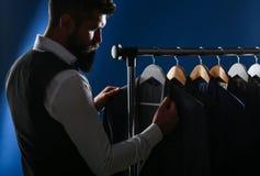 Uomo d'affari in maglia, fila dei vestiti in negozio Uomo alla moda in un rivestimento del panno È nella sala d'esposizione, prov fotografia stock