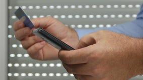 Uomo d'affari Make Online Payment facendo uso di un cellulare e di una carta di credito video d archivio