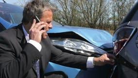 Uomo d'affari Making Phone Call dopo l'incidente di traffico video d archivio