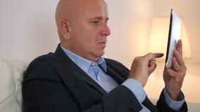 Uomo d'affari Managing un affare facendo uso della comunicazione senza fili della compressa elettronica archivi video