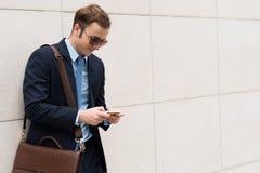 Uomo d'affari mandante un sms Immagine Stock