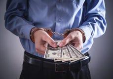 Uomo d'affari in manette con i dollari Crimine di affari immagini stock