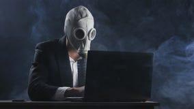 Uomo d'affari in maschera antigas che funziona al computer portatile in ufficio in fumo stock footage