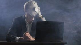 Uomo d'affari in maschera antigas che funziona al computer portatile in ufficio in fumo video d archivio