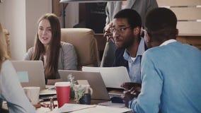 Uomo d'affari maschio afroamericano che conduce una sessione di 'brainstorming' al movimento lento multietnico di riunione del gr archivi video