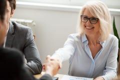 Uomo d'affari maturo attraente sorridente di handshake della donna di affari immagine stock libera da diritti