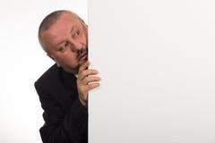 Uomo d'affari maturo che giudica un pannello e gesturing bianchi isolati su fondo bianco Immagini Stock