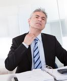 Uomo d'affari maturo che ritiene scomodo Immagini Stock