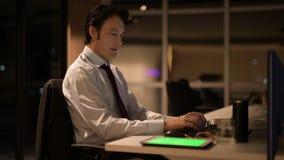 Uomo d'affari maturo che si siede e che lavora nell'ufficio alla notte archivi video