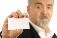 Uomo d'affari maturo che tiene biglietto da visita in bianco Fotografia Stock