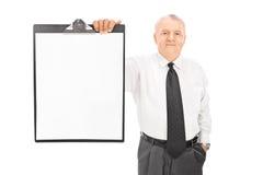 Uomo d'affari maturo che tiene carta in bianco sulla lavagna per appunti Fotografie Stock