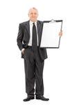Uomo d'affari maturo che tiene una lavagna per appunti enorme Fotografie Stock