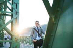 Uomo d'affari maturo con uno smartphone in una città fotografia stock
