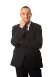 Uomo d'affari maturo felice con la mano sotto il mento Fotografia Stock
