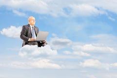 Uomo d'affari maturo nel volo del vestito sulle nuvole con il computer portatile fuori immagini stock libere da diritti