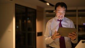 Uomo d'affari maturo sollecitato in ufficio alla notte facendo uso del computer digitale della compressa stock footage