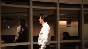 Uomo d'affari maturo in ufficio alla notte che guarda con la finestra e pensare archivi video
