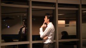 Uomo d'affari maturo in ufficio alla notte che guarda con la finestra e pensare video d archivio