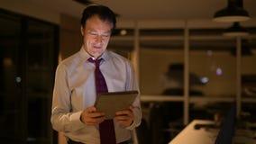 Uomo d'affari maturo in ufficio alla notte facendo uso del computer digitale della compressa video d archivio