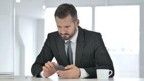 Uomo d'affari Medio Evo Using Phone per la lettura del email stock footage