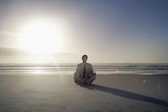 Uomo d'affari Meditating In Lotus Position On Beach Immagini Stock