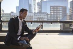 Uomo d'affari millenario che porta vestito nero e camicia bianca che si siedono sull'argine del Tamigi facendo uso dello smartpho immagine stock