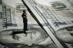 Uomo d'affari miniatura della figurina con 100 dollari di banconota su fondo Fotografia Stock