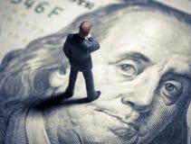 Uomo d'affari miniatura della figurina con 100 dollari Vista superiore Fotografie Stock