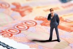 Uomo d'affari miniatura della figurina con 5000 rubli di banconota su fondo Fotografia Stock Libera da Diritti