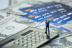Uomo d'affari miniatura di fiducia che sta e che pensa sul calcolatore nero sul mucchio di usando dei soldi delle carte di credit immagini stock