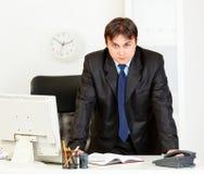 Uomo d'affari moderno rigoroso che si leva in piedi alla scrivania Fotografia Stock