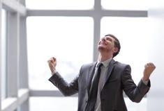 Uomo d'affari molto felice che sta nell'ufficio Foto con lo spazio della copia immagini stock libere da diritti