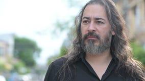Uomo d'affari multi-etnico barbuto bello maturo con capelli lunghi nelle vie all'aperto video d archivio