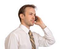 Uomo d'affari nei colloqui bianchi della camicia sul telefono Fotografie Stock