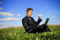 Uomo d'affari nel mezzo del campo sul computer portatile Fotografie Stock Libere da Diritti