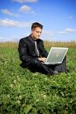 Uomo d'affari nel mezzo del campo sul computer portatile Fotografia Stock Libera da Diritti