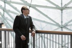 Uomo d'affari nell'usura convenzionale che riposa e che guarda Fotografia Stock Libera da Diritti
