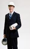 Uomo d'affari nelle cianografie della holding dell'elmetto protettivo Immagine Stock