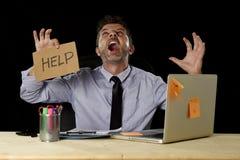 Uomo d'affari nello sforzo che lavora al segno della tenuta dello scrittorio del computer di ufficio che chiede i grida di aiuto  immagine stock