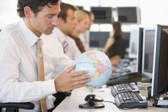 Uomo d'affari nello spazio di ufficio con un globo dello scrittorio fotografie stock libere da diritti
