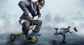Uomo d'affari nerd che guida una piccola bicicletta fotografia stock