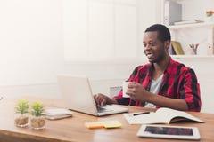 Uomo d'affari nero felice in ufficio casuale, lavoro con il computer portatile Fotografia Stock
