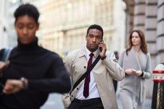 Uomo d'affari nero millenario che cammina in una via occupata di Londra facendo uso dello smartphone, fuoco selettivo immagini stock libere da diritti