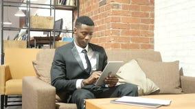 Uomo d'affari nero Using Tablet, dell'interno stock footage