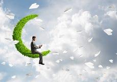 Uomo d'affari o studente che si siede sulla luna verde e che fa le chiamate immagine stock libera da diritti