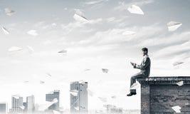 Uomo d'affari o studente sul bordo del tetto che fa le chiamate e paesaggio urbano a fotografia stock libera da diritti