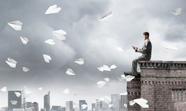 Uomo d'affari o studente sul bordo del tetto che fa le chiamate e paesaggio urbano al fondo fotografie stock libere da diritti