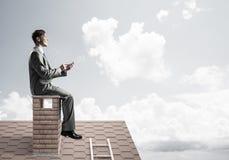 Uomo d'affari o studente sul tetto del mattone che sorride e che fa le chiamate fotografia stock libera da diritti