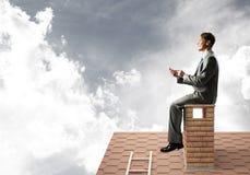 Uomo d'affari o studente sul tetto del mattone che sorride e che fa le chiamate immagine stock libera da diritti
