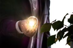 Uomo d'affari o uomo in un vestito che tiene una lampadina fotografia stock libera da diritti